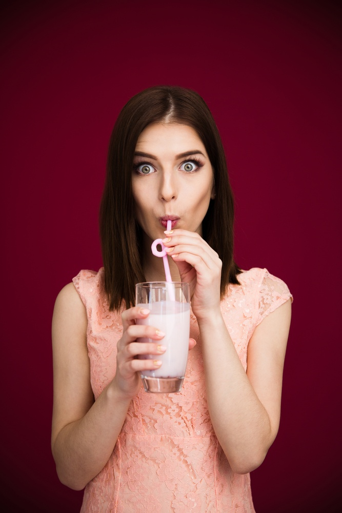 Young pretty woman drinking yogurt over pink background and looking at camera.jpeg